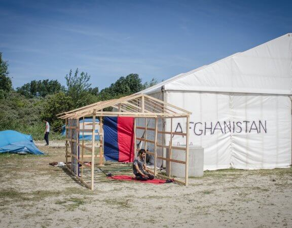 1452274_by_thom_davies___an_afghan_refugee_prays_in_the_calais__jungle__camp