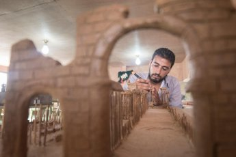 "Mahmoud built his model of Palmyra using clay and wooden kebab skewers. Mahmoud, who like the other artists is also from Dara'a, hopes that by seeing the exhibition, residents at Za'atari will remain connected with the country and culture they have been forced to leave behind. ""This is a way for them not to forget. As artists we have an important role to play. A lot of what we know about ancient civilisations or prehistoric people is preserved through their art – Egyptian hieroglyphs or cave paintings."""