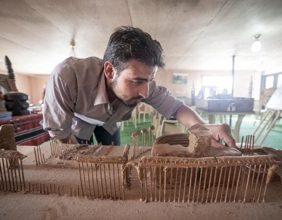 """Mahmoud Hariri, 25, was an art teacher and painter back in Syria before coming to Za'atari in 2013 to escape the violence.   """"When I first arrived I didn't think I would continue my work as I only expected to be here for a week or two. But when I realised it would be years, I knew I had to start again or lose my skills.""""   He built his model of Palmyra using clay and wooden kebab skewers. He only found out last month that the site had fallen under the control of ISIS.   """"We haven't had electricity in the camp recently, so I hadn't seen the news. I'm very worried about what might happen. This site represents our history and culture, not just for Syrians but all of humanity. If it is destroyed it can never be rebuilt."""""""